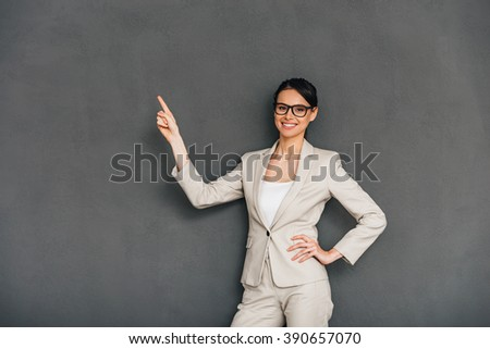 Take a look here! Cheerful young businesswoman in glasses pointing on copy space and looking at camera with smile while standing against grey background - stock photo