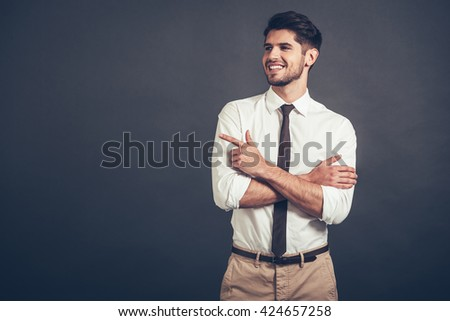 Take a look here! Confident young handsome man pointing at copy space with smile while standing against grey background - stock photo