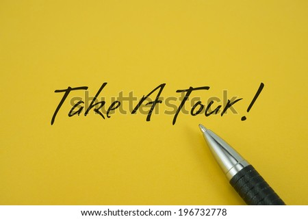 Take A Tour! note with pen on yellow background
