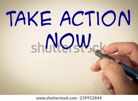 Take action now text write on wall  - stock photo