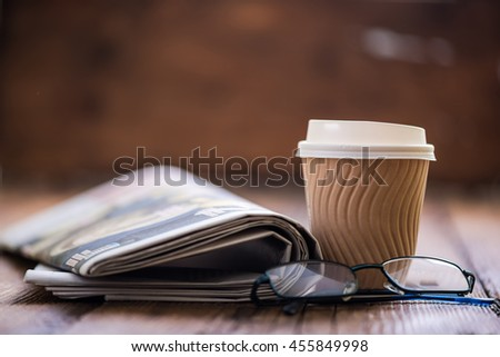 take away coffee and newspaper with reading glasses