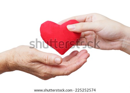take care of old mother - young female hand giving a red heart to old hand of a mother - stock photo