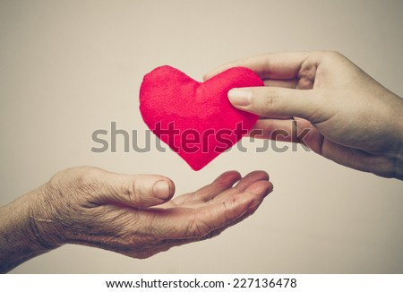 take care of old mother - young female hand giving a red heart to old hand of a mother - happy mother's day - stock photo