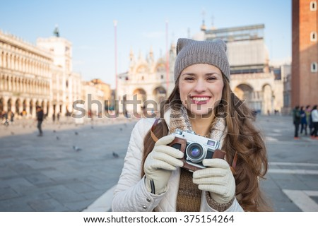 Take classical tourist enjoyment in Venice, Italy - wander over San Marco square, chase pigeons and take photos. Portrait of happy young woman with retro photo camera on Piazza San Marco - stock photo