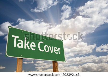Take Cover Green Road Sign with Dramatic Clouds and Sky.