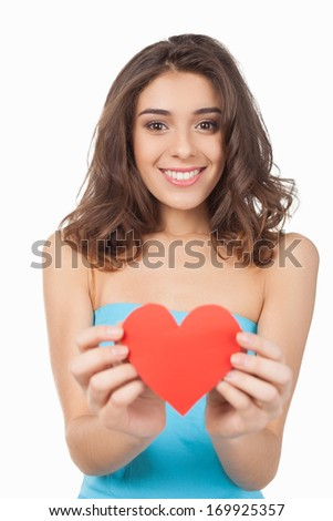 Take my love! Attractive young woman holding a red paper heart and smiling at camera while standing isolated on white background
