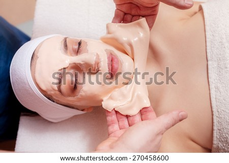 take off the mask for the face of a beautiful girl in spa salon - stock photo
