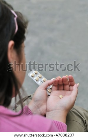 Take or not - young woman  (teenage girl) decides while holding pills, focus on hands
