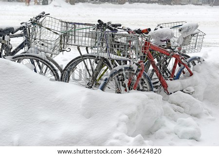 Take out delivery bicycles locked on sidewalk and covered in snow after blizzard, Manhattan New York City - stock photo