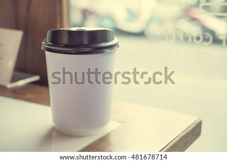 Take-out hot coffee cup on the table near window