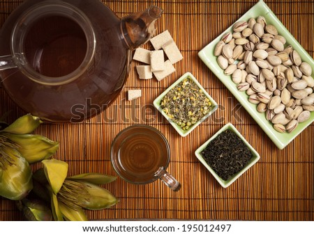 Take the tea, above view. Preparation of tea in a teapot, cup of tea, sugar, choice of green tea and herb tea and pistachio nuts on wooden placemat.