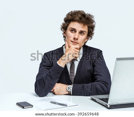 Take thought. Young Businessman at the workplace working with computer on gray background. - stock photo