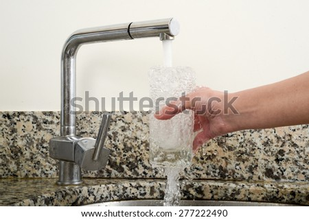 Take water in glass from a tap - stock photo
