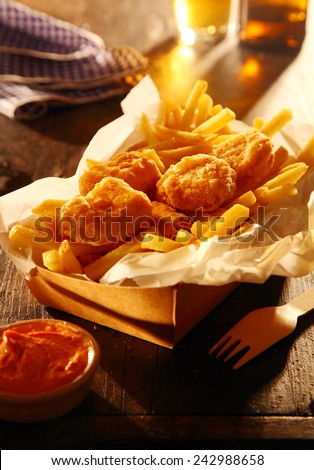 Takeaway carton of fried fish in crispy batter with French fries and a dipping sauce served with beer in a pub or cafeteria - stock photo