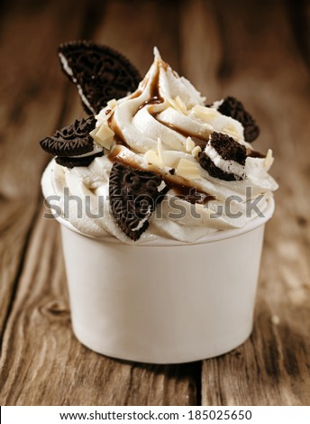Takeaway tub filled with a swirl of vanilla ice cream with pieces of oreo biscuits and chocolate sauce, close up view on old wooden boards - stock photo
