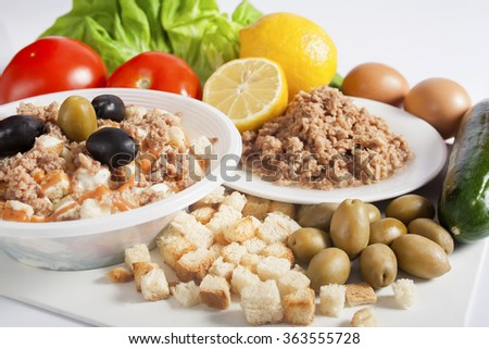 Takeaway tuna salad served in a white plastic bowl next to a white plate with tuna chunks, lemon, olives, croutons, and fresh eggs, cucumbers, tomatoes and lettuce. - stock photo