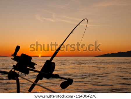 Taken just off the coast of Vancouver Island the silhouette of a down rigging fishing rod at sunset. - stock photo