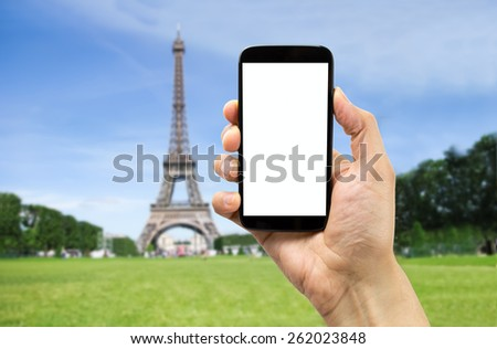 takin a photograph of the eiffel tower in paris with one smartphone - stock photo