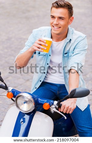 Taking a break to drink coffee. Top view of happy young man sitting on scooter and drinking coffee  - stock photo
