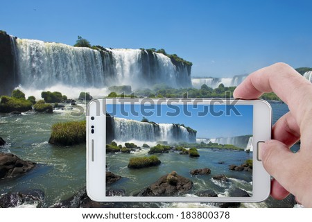 Taking a picture at the footbridge over the magnificent garganta del diablo at the iguazu falls, one of the seven natural wonders of the world - stock photo