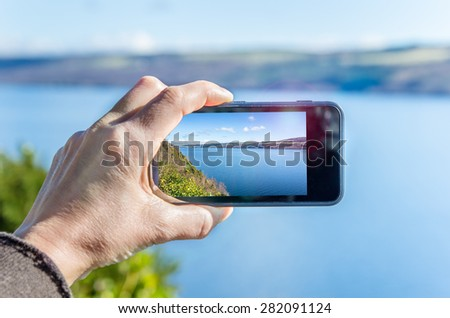 Taking a Picture of Loch Ness with a Mobile Phone. Shallow Deep of Field and Sun Glare on the Phone. - stock photo