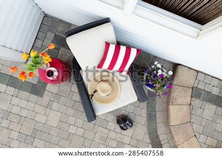 Taking a relaxing tea break in a deep seating patio set with a comfortable armchair flanked by colorful spring flowers with a sunhat and garden shoes on a brick paved outdoor patio, overhead view - stock photo