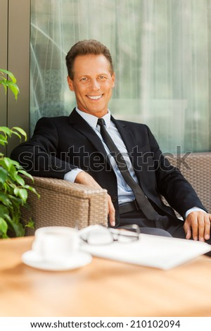 Taking a rest after business meeting. Cheerful mature man in formalwear looking at camera and smiling while sitting at the chair outdoors with coffee cup on foreground - stock photo
