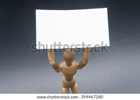 Taking a stand/Conceptual image using a wooden dummy as subject and representing a person holding a white banner above his head.