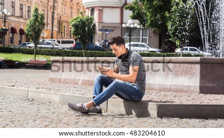 Taking a time for respite. Young handsome man holding smart phone and smiling while sitting on the pavement.