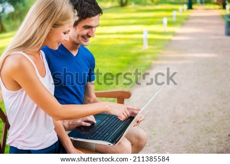 Taking advantages of digital age. Side view of beautiful young loving couple sitting on the bench together and looking at laptop  - stock photo