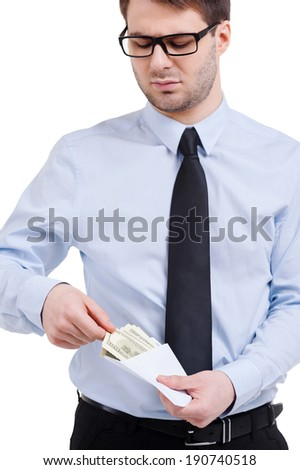 Taking bribe. Young man in shirt and tie taking money from the envelope while standing isolated on white - stock photo