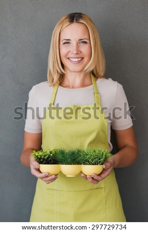 Taking care for environment. Smiling mature woman in green apron holding flower pot and looking at camera while standing against grey background  - stock photo