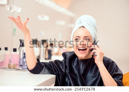 Taking care of business in the stylists chair. Beautiful emotional businesswoman talking over her mobile phone while sitting with a towel on her head at the hair salon  - stock photo