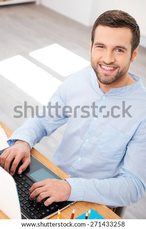 Taking care of business with smile. Top view of handsome young man in shirt working on laptop and smiling at camera while sitting at his working place - stock photo