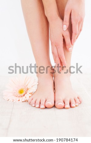 Taking care of her feet. Close-up of young woman touching her feet while standing on hardwood floor - stock photo
