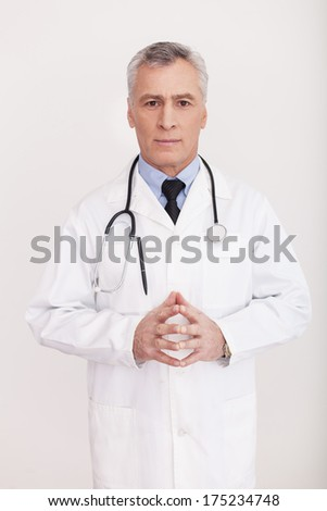 Taking care of your health. Senior grey hair doctor in uniform looking at camera and keeping hands clasped while standing isolated on white