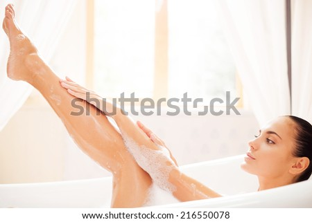 Taking good care of her skin. Side view of attractive young woman touching her leg while enjoying luxurious bath - stock photo
