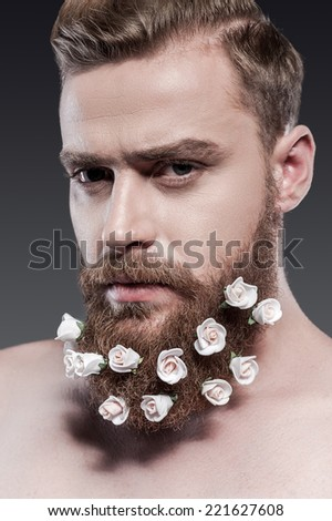 Taking good care of his beard. Portrait of handsome young shirtless man with flowers in his beard looking at camera while standing against grey background