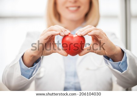 Taking good care of your heart. Close-up of female doctor in white uniform holding heart prop and smiling - stock photo