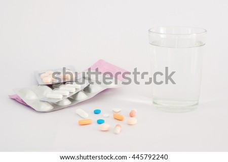 Taking medicine with a glass of water on white background - stock photo