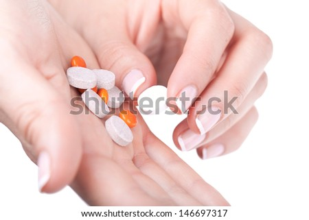 Taking one pill from pile, closeup on white