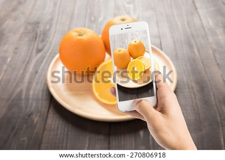Taking photo of fresh oranges on wooden dish, fresh fruits on wooden background - stock photo