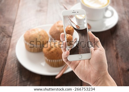 Taking photo of muffin and coffee on wooden table. - stock photo