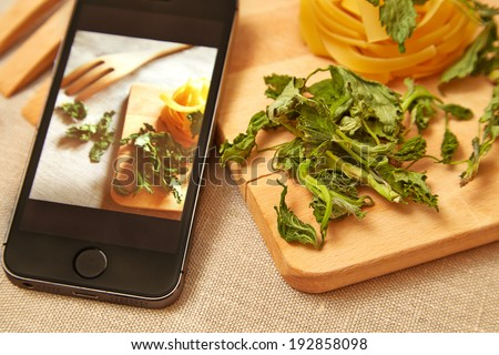 Taking photo of raw pasta with smartphone - stock photo