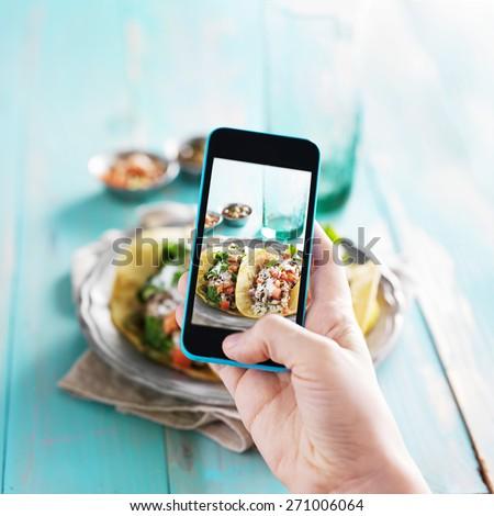 taking photo of tacos with smart phone - stock photo