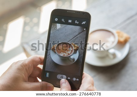 Taking photo of the latte with mobile phone