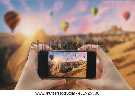 Taking photo on smart phone concept.Hot air balloon flying over spectacular Cappadocia.