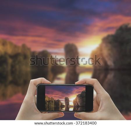 Taking photo on smart phone concept.Sunset James Bond island near Phuket in Thailand. - stock photo