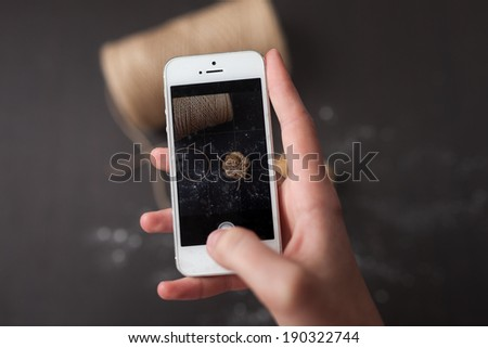 Taking picture with smartphone on woodem background - stock photo
