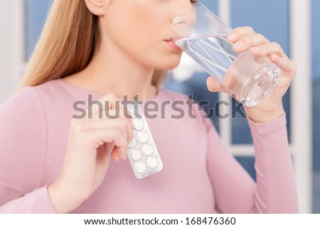 Taking pills. Cropped image of young woman taking pills and drinking water  - stock photo